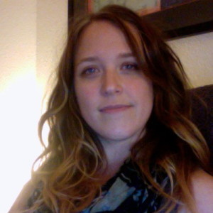 Image description: A picture of Jess Hughes' head and shoulders. She's a white woman with long, wavy brown hair and a slight smile.