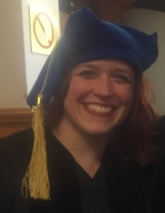 A picture of Jess Hughes on her graduation day. She's wearing a black robe and a floppy, blue velvet hat with a gold tassle and a big smile.